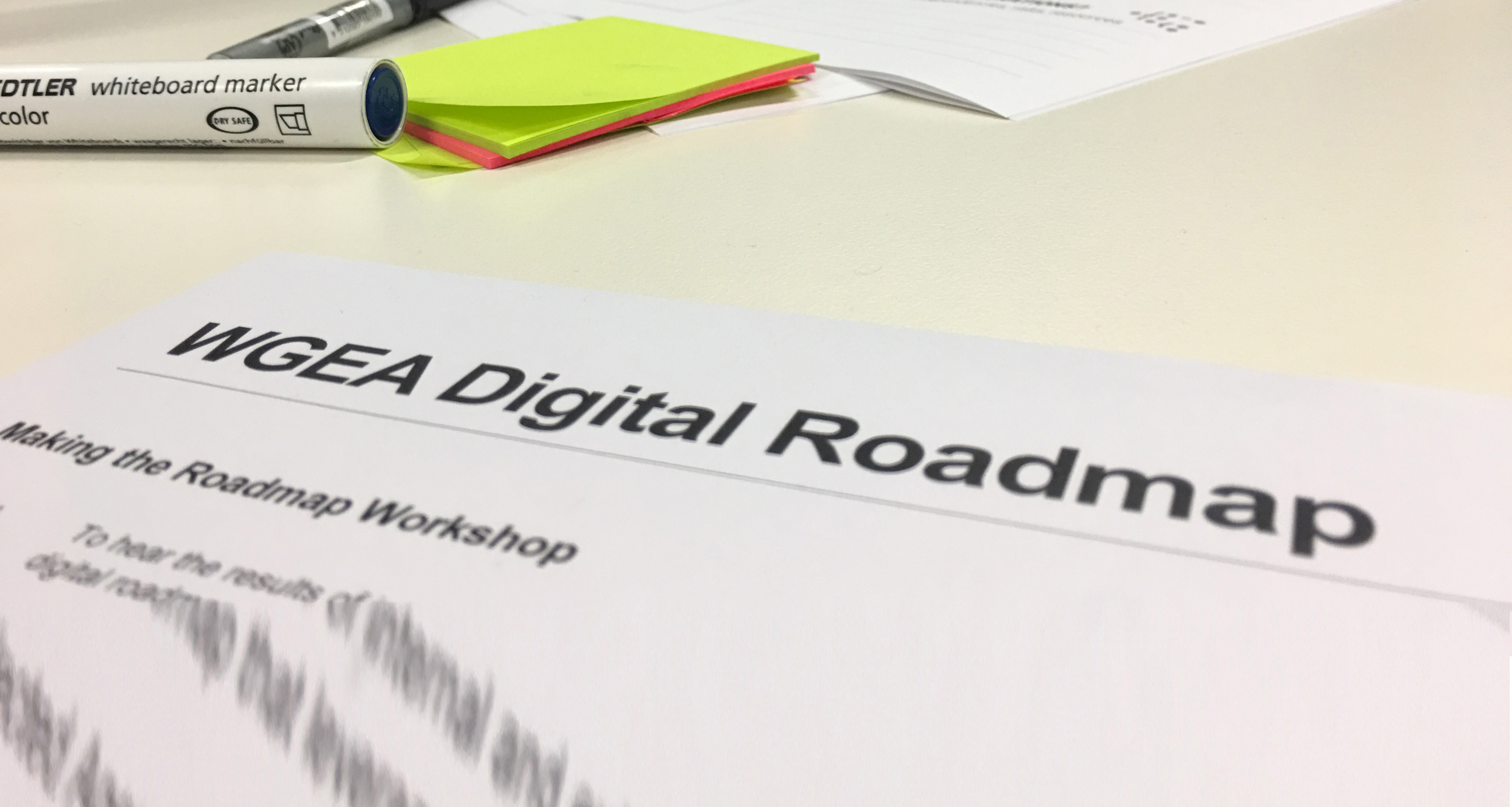 """Image of area of tabletop with markers and sticky notes and part of a page titled """"WGEA Digital Roadmap"""""""